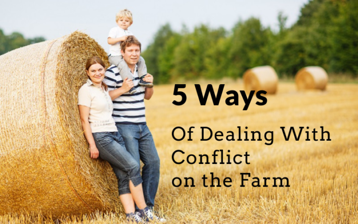 a happy family with young children on the farm leaning on a hay bale